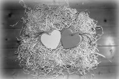 Corazones de madera grises en blanco del amor junto Imagenes de archivo