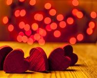 Corazones de madera rojos con las luces en el fondo Foto de archivo libre de regalías