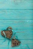 Corazones de mimbre decorativos del color gris con una cinta azul en un w Fotografía de archivo libre de regalías