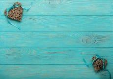 Corazones de mimbre decorativos del color gris con una cinta azul en un w Foto de archivo
