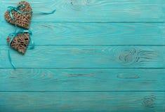 Corazones de mimbre decorativos del color gris con una cinta azul en un w Fotos de archivo libres de regalías
