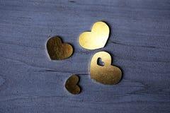 Corazones de oro en una tabla de madera Imagenes de archivo