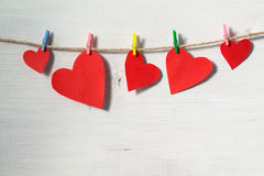 Corazones de papel brillantes rojos que cuelgan en cuerda en un fondo de madera blanco Imagenes de archivo