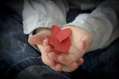 Corazones de papel en la mano de un niño Imagen de archivo