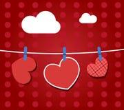 Corazones de papel que cuelgan de una cuerda, en el papel pintado rojo Parte del conjunto del día de tarjetas del día de San Vale Fotos de archivo libres de regalías