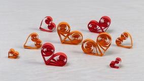 Corazones de papel rojos y anaranjados hechos a mano en técnica quilling Foto de archivo libre de regalías