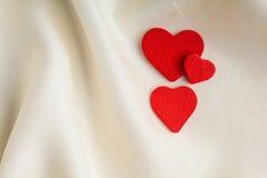 Corazones decorativos de madera rojos en el fondo de seda blanco. Imagen de archivo