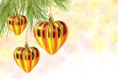 Corazones del â de las bolas de la Navidad en la ramificación de árbol de pino Imágenes de archivo libres de regalías