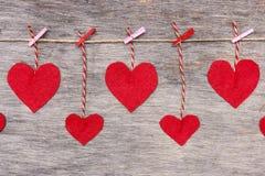 Corazones del amor de la tarjeta del día de San Valentín roja en el cordón natural y los pernos rosados que cuelgan en el fondo r foto de archivo libre de regalías