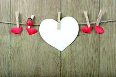 Corazones del amor que cuelgan en cuerda en un fondo de madera Concepto del amor Corazón verde estilizado de la ilustración del v foto de archivo