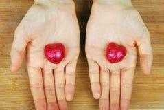 corazones del caramelo en el fondo en manos femeninas Fotografía de archivo libre de regalías