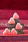 Corazones del caramelo en una pila de pedazos oscuros del chocolate fotos de archivo