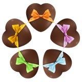 Corazones del chocolate con el arco aislado en blanco Fotografía de archivo