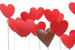 Corazones del día de tarjeta del día de San Valentín en un palillo con el corazón del chocolate Imagen de archivo