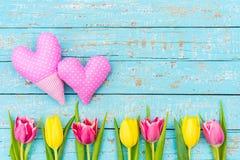 Corazones del día del ` s de la tarjeta del día de San Valentín y flores de los tulipanes en la madera azul clara con el espacio  Fotos de archivo
