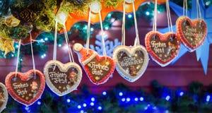 Corazones del pan de jengibre en fila que dicen ` del ` buenas fiestas Imágenes de archivo libres de regalías