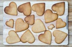 Corazones del pan de jengibre en un tablero de madera Fotografía de archivo libre de regalías