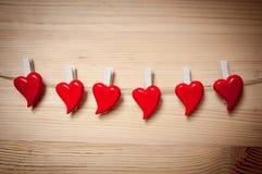 Corazones del ` s de la tarjeta del día de San Valentín que cuelgan sobre fondo de madera foto de archivo libre de regalías
