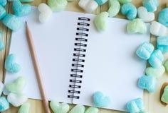 Corazones del verde azul y cuaderno en blanco con el lápiz en tono suave Foto de archivo