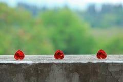 3 corazones en los floorhearts del cemento en el cemento suelan el fondo verde Imagen de archivo libre de regalías
