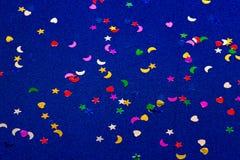 Corazones, estrellas y lunas del witl del fondo el chispear y del brillo del azul pequeños Visión superior Fotografía de archivo libre de regalías