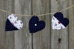 Corazones florales de la tela que cuelgan en cuerda para tender la ropa por el fondo de madera lamentable Imágenes de archivo libres de regalías