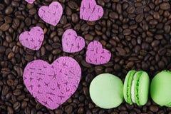 Corazones grandes y pequeños y macarrones verdes de la galleta tres en fondo del café Imágenes de archivo libres de regalías