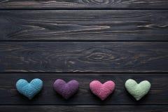 Corazones hecho a ganchillos coloridos en la tabla de madera gris rústica Foto de archivo