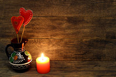 Corazones hechos a mano decorativos y vela ardiente Fotos de archivo