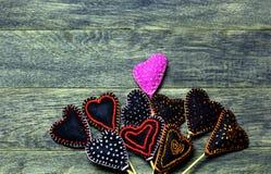 Corazones hechos a mano del fieltro en viejo fondo de madera oscuro Foto de archivo libre de regalías