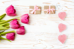 Corazones hechos punto, regalos con una cinta rosada y un ramo de tulipanes en un fondo de madera blanco Foto de archivo libre de regalías