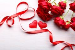 Corazones rojos, cinta y rosas hermosas en la tabla de madera Imágenes de archivo libres de regalías