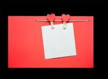 Corazones rojos con las pinzas que cuelgan en la cuerda para tender la ropa aislada en fondo negro Foto de archivo libre de regalías