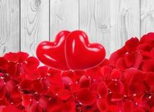 Corazones rojos con los pétalos color de rosa rojos hermosos en de madera blanco Fotografía de archivo libre de regalías