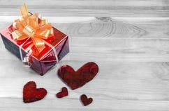 Corazones rojos rojos de la caja de regalo en lugar blanco y negro del fondo bajo texto foto de archivo libre de regalías
