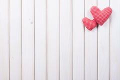 Corazones rojos de la tela escocesa en la cerca blanca Imágenes de archivo libres de regalías