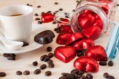 Corazones rojos del chocolate en un tarro de cristal y un café del café express Fotografía de archivo libre de regalías
