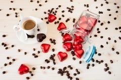 Corazones rojos del chocolate en un tarro de cristal y una taza de café del café express Fotografía de archivo libre de regalías