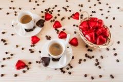 Corazones rojos del chocolate en una pequeña cesta y dos tazas de café Imagen de archivo