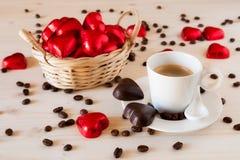Corazones rojos del chocolate en una pequeña cesta y un café del café express Imagen de archivo