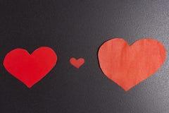 Corazones rojos del documento sobre fondo negro concepto de amor y de día del ` s de la tarjeta del día de San Valentín del St id Fotos de archivo