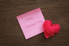 Corazones rojos del lunar con la nota de la tarjeta del día de San Valentín sobre la textura de madera Fotos de archivo libres de regalías