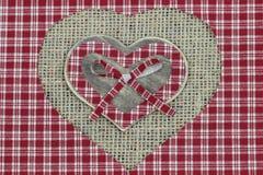 Corazones rojos del país de la tela escocesa y de madera con el fondo lamentable de la arpillera Fotografía de archivo