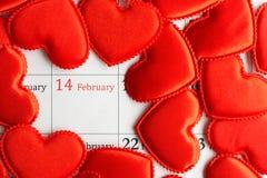 Corazones rojos del paño en el calendario Imagen de archivo libre de regalías