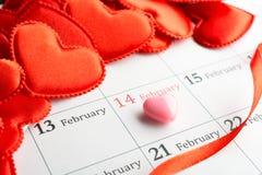 Corazones rojos del paño en el calendario Imágenes de archivo libres de regalías