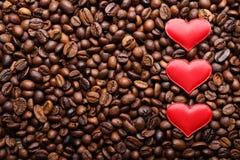 Corazones rojos en fondo de los granos de café Imagenes de archivo