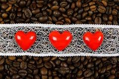 Corazones rojos en la tira blanca en el fondo de los granos de café Foto de archivo
