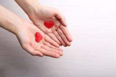 Corazones rojos en manos femeninas Imagen de archivo
