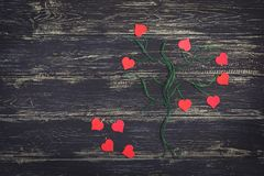 Corazones rojos en un árbol del hilo Imagen de un árbol con los corazones rojos en un fondo de madera negro Foto de archivo