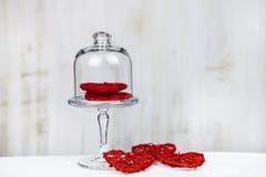 Corazones rojos en un plato de cristal fotos de archivo